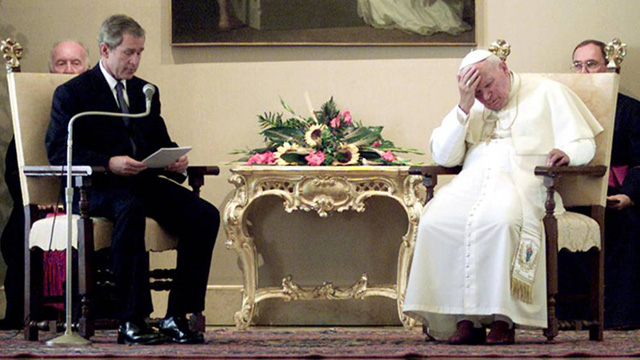 The Pope sits across from George Bush with a pained look on his face